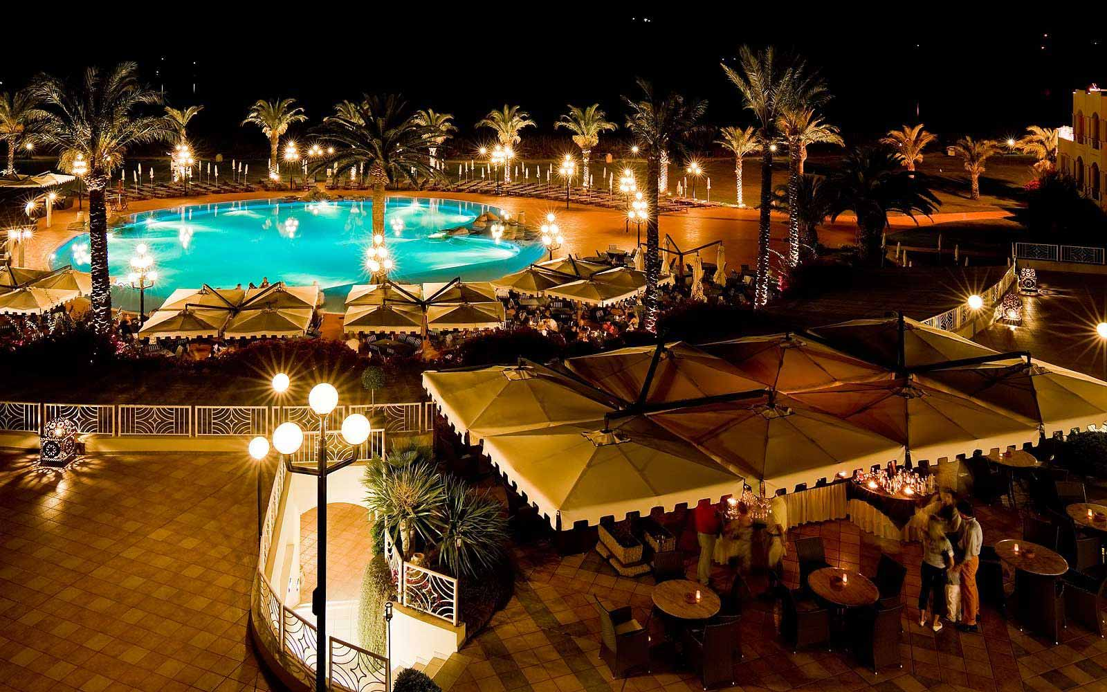 Pullman Timi Ama Sardegna's swimming pool area at night