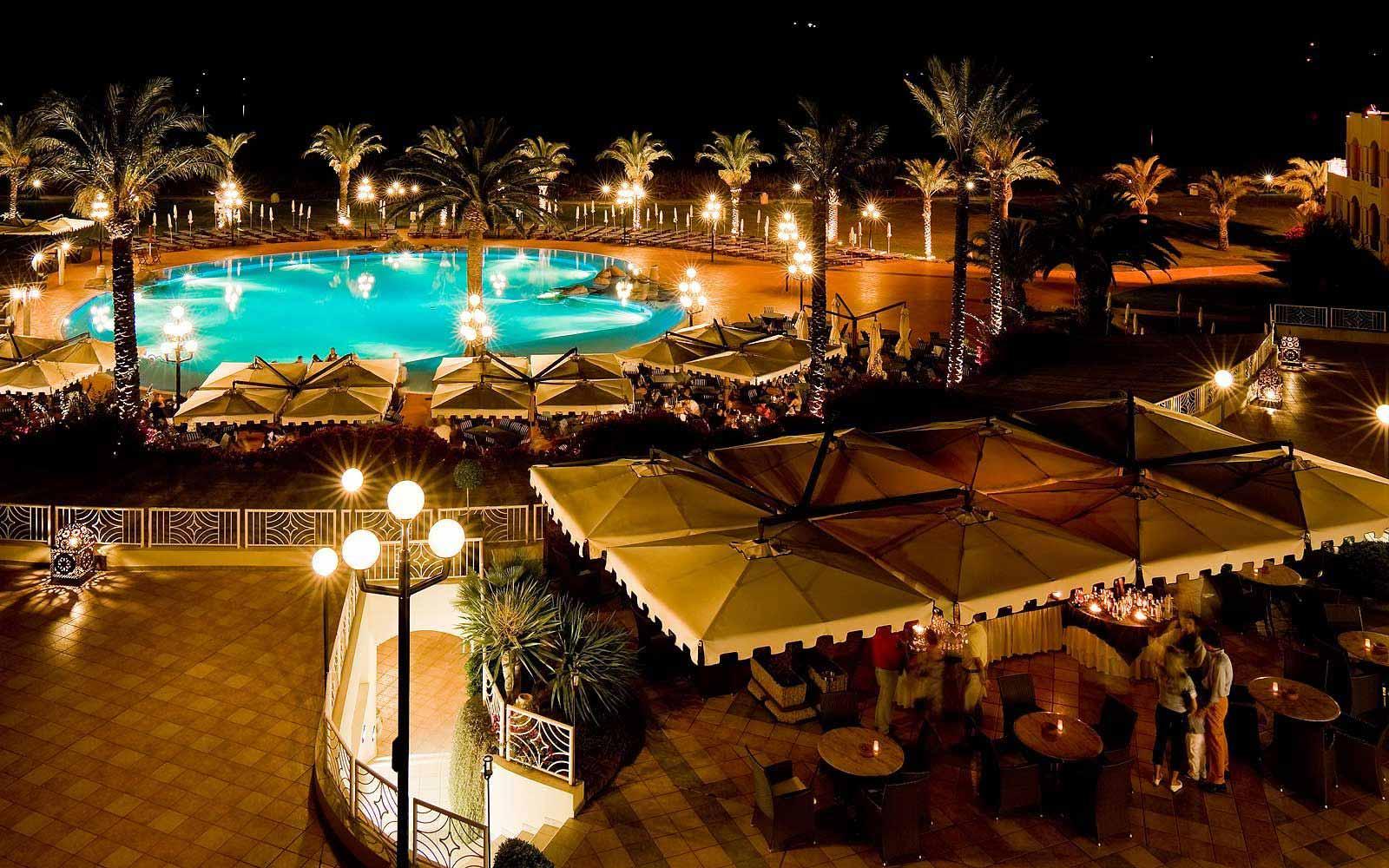 Pullman Timi Ama Sardegna's swimming pool area at night