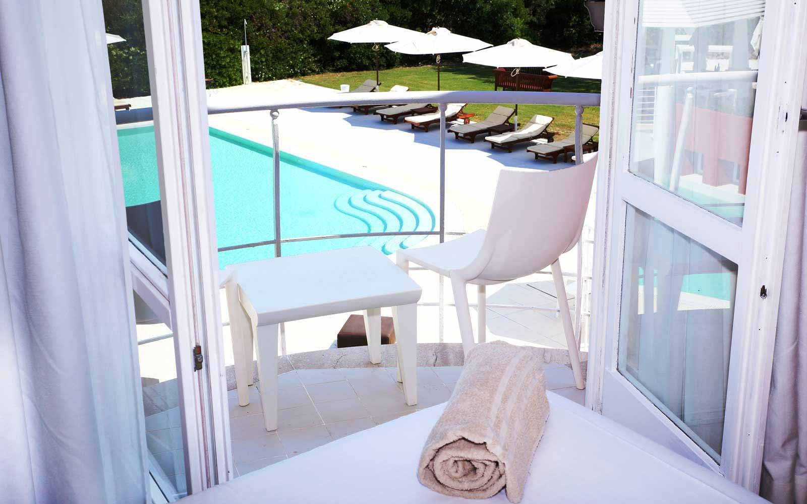 Balcony overlooking the pool in a Superior Room at La Coluccia Hotel & Beach Club