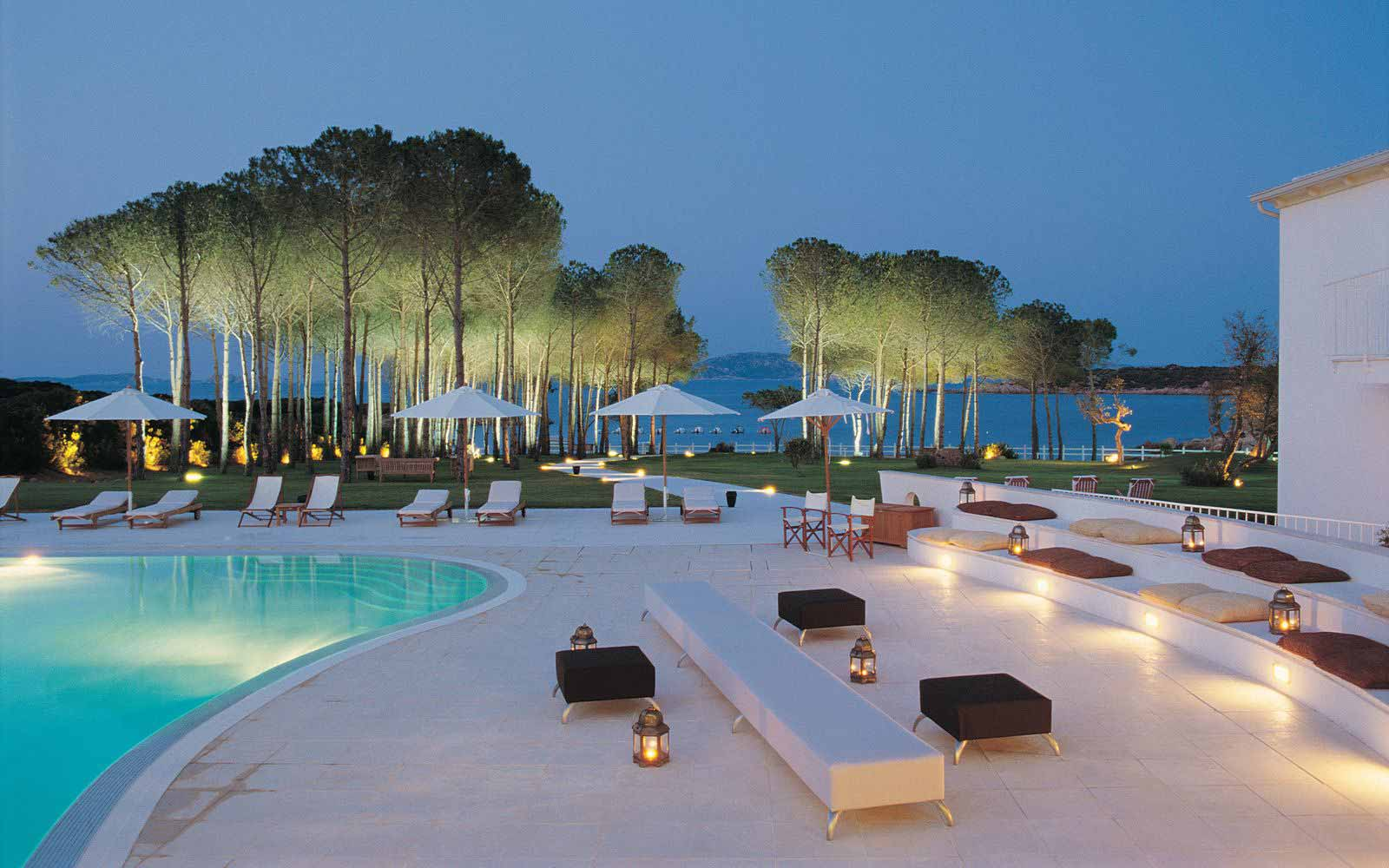Swimming pool by night at La Coluccia Hotel & Beach Club