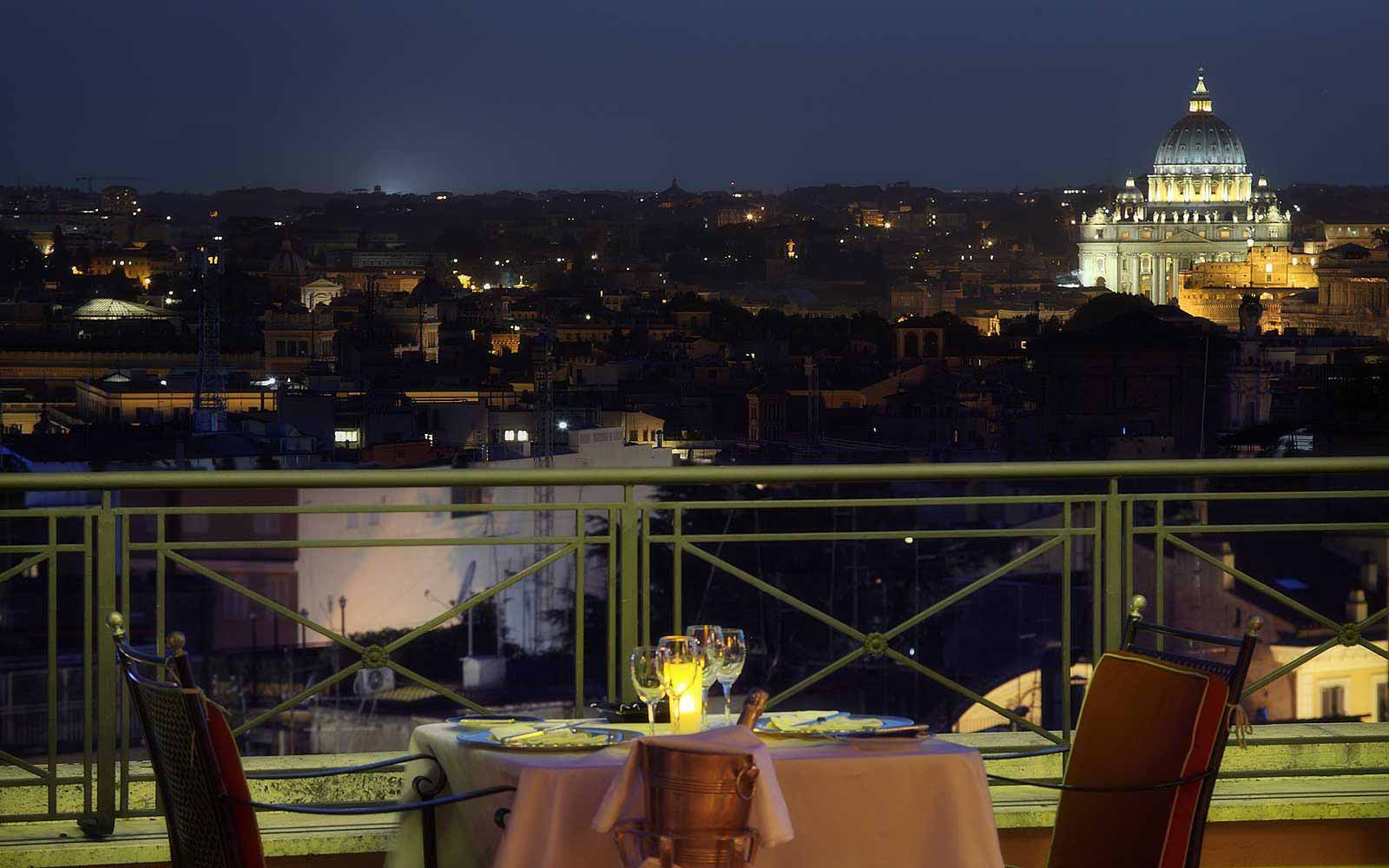 Rooftop restaurant L'Olimpo at Hotel Bernini Bristol with a view of St. Peter's at night
