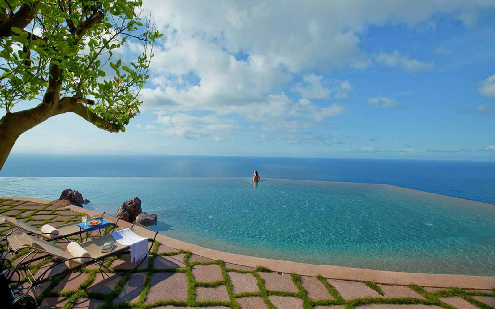 Infinity pool merging with the sea at Monastero Santa Rosa