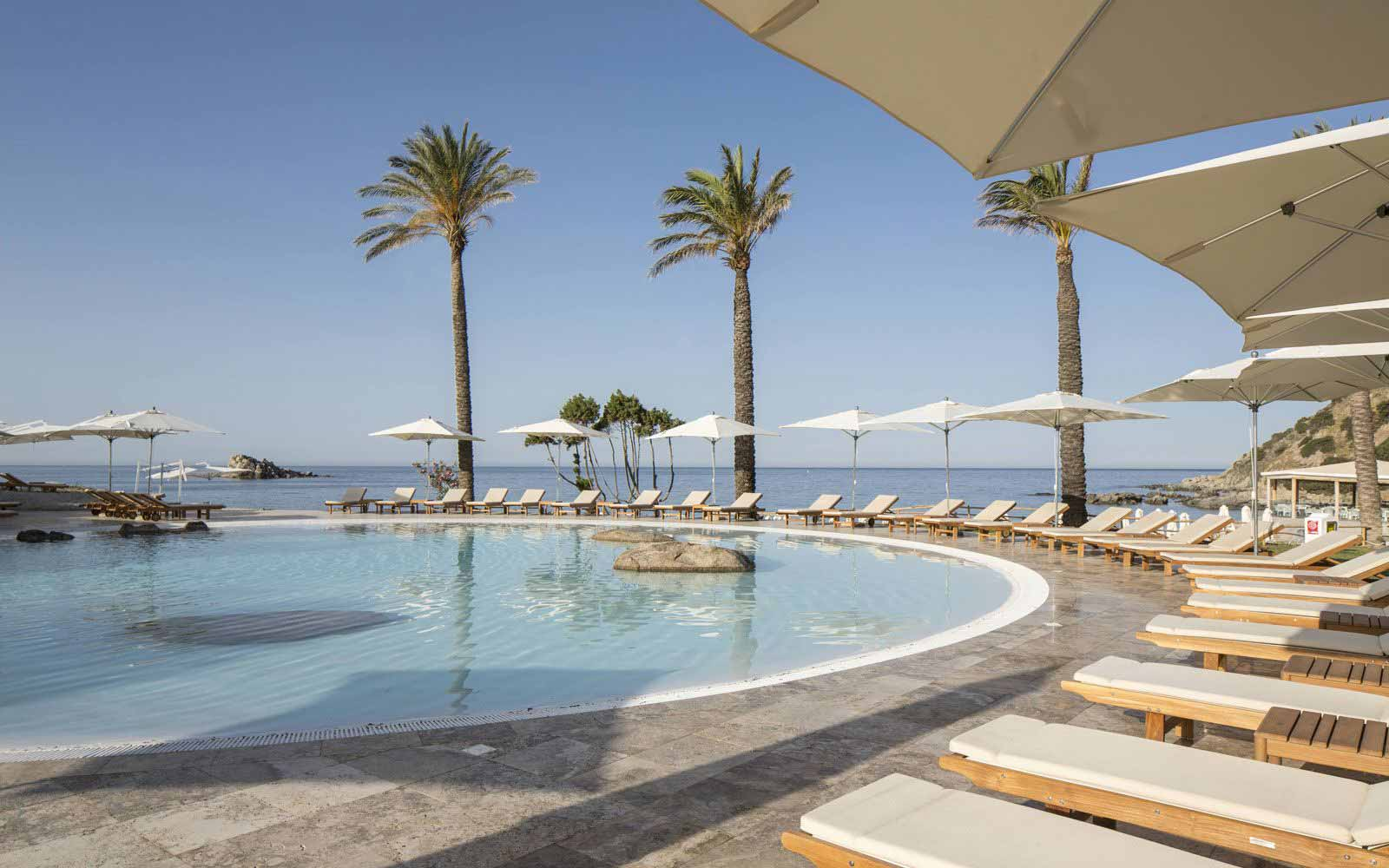 Swimming pool and solarium at Falkensteiner Resort Capo Boi